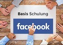 """Holztisch mit großem Papier in der Mitte, außen herum Hände, Aufschrift """"Basis Schulung Facebook Fanpage"""""""