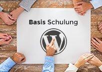 """Holztisch mit großem Papier in der Mitte, außen herum Hände, Aufschrift """"Basis Schulung WordPress"""""""