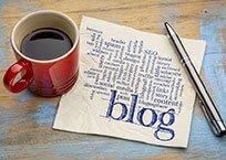 """Kaffeetasse steht auf Blatt Papier mit Beschriftung """"Blog"""" und Stift daneben"""