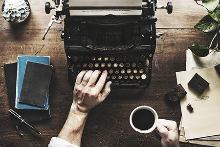 Mann schreibt auf alter Schreibmaschine, in der anderen Hand einen Kaffee