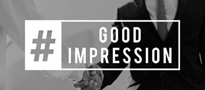 """Zwei Geschäftsleute schütteln sich die Hände, Banner im Vordergrund mit Aufschrift """"Good Impression"""""""