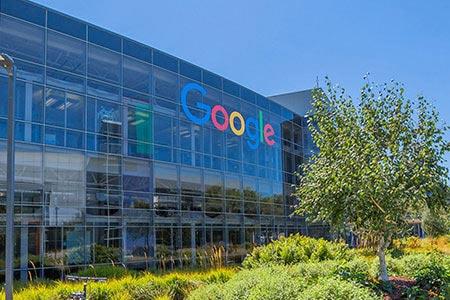 Kleiner Ausschnitt der Außenansicht der Google Firmenzentrale mit Schriftzug an der Glasfassade