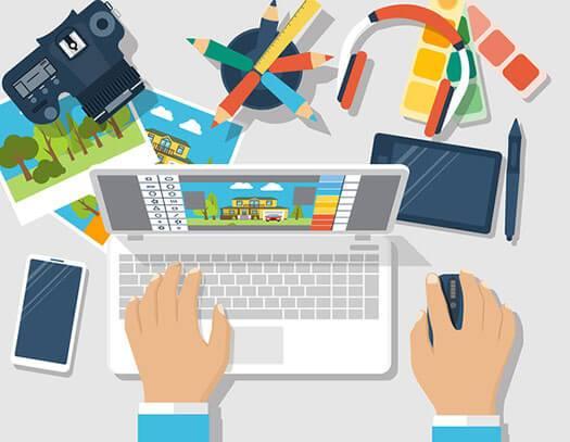 Webdesign mit Laptop und Kamera auf einem Tisch, Farbtabellen und Stifte liegen herum, illustriert