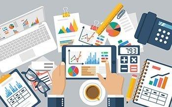 Tisch mit Charts, Analysen und Graphen auf Blättern und Tablet